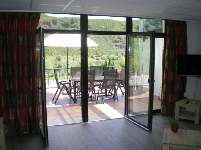 Terasse mit Gartenmöbeln und Sonnenschirm am deutschen Gruppenhaus Moselschleife direkt am Weinberg.
