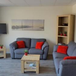 Gruppenraum mit TV und Sofas im deutschen Freizeithaus Moselschleife an der Mosel.