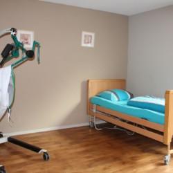 Ein Pflegebett mit Lifter im niederländischen Gruppenhaus Kievitsnest.