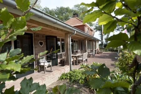 Außenansicht mit schöner sonniger Terasse vom Handicaphaus für behinderte Menschen in den Niederlanden Het Keampke Meidoorn