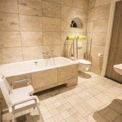 Barrierefreies und rollstuhlgerechtes Bad mit unterfahrbarer Badewanne und Duschstuhl im Freizeitheim De Sterre in den Niederlanden.