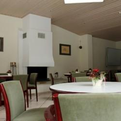 Ein Gruppenraum mit Kamin und Sitzgruppen im deutschen Gruppenhaus Gästehaus Horn-Bad Meinberg für barrierefreie Gruppenreisen.