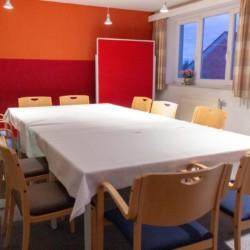 Gruppenraum mit Sitzgruppe und Pinnwand im deutschen Freizeithaus Hotel Rügenblick in Deutschland an der Ostsee.