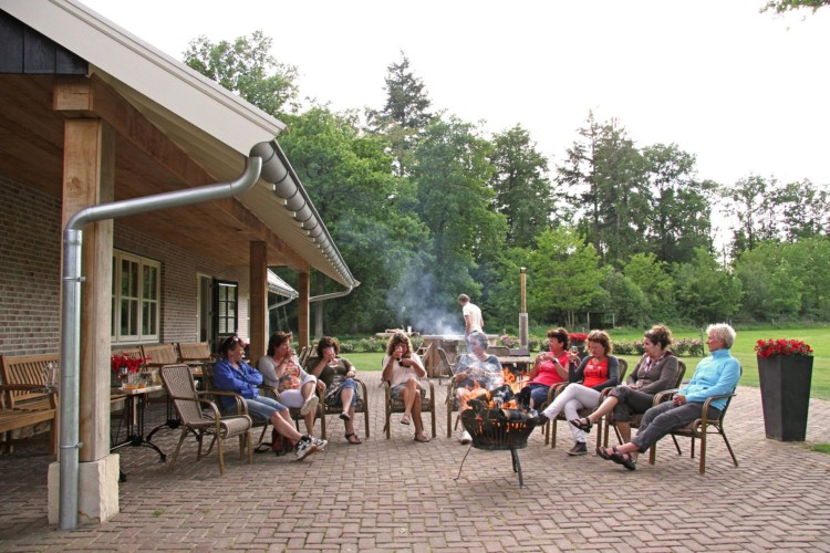 Terasse mit Gartenmöbeln und Lagerfeuer am niederländischen Freizeitheim De Sterre.