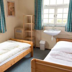 Ein Schlafzimmer mit Einzelbetten und Waschbecken im Gruppenhaus De Boerschop in den Niederlanden.